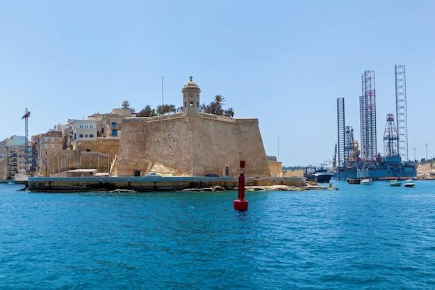 Structuren met apparatuur voor het boren van oliebronnen bevinden zich in de zee nabij een kust van malta