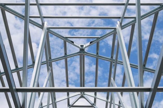 Structuur van stalen dakframe met blauwe lucht en wolken