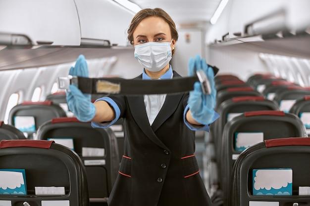 Stuardess in mask toont demo voor vlieg