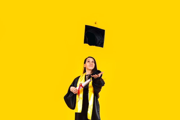 Studeer af met een diploma, gooi haar afstudeerpet in de lucht en vier feest boven de gele muur