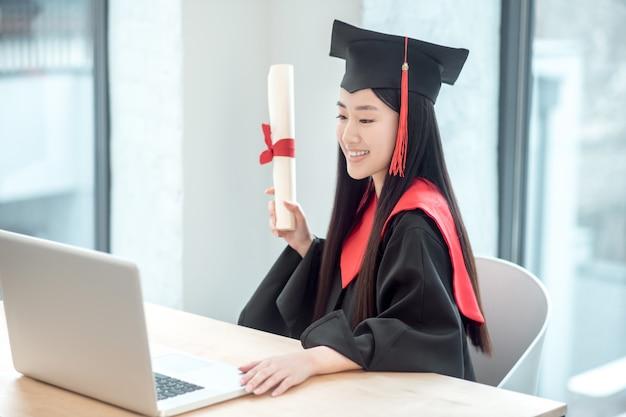 Studeer af met een diploma. leuke aziatische glimlachende gediplomeerde die haar diploma houdt en een videogesprek heeft