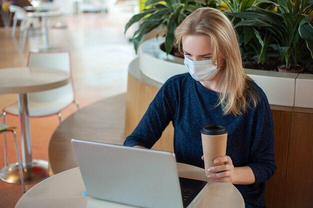Studeer en werk tijdens de epidemie. sociale afstand. een blonde vrouw zit aan een tafel in een leeg café.