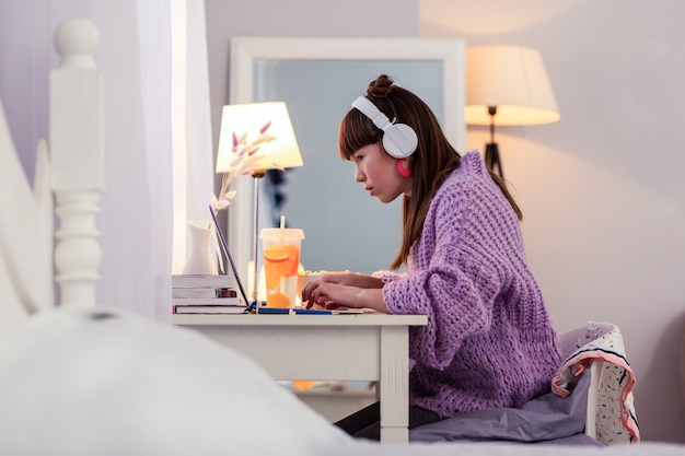 Studeer goed. ernstige leerling met koptelefoon tijdens het kijken naar video