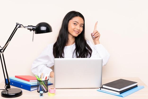 Student aziatisch meisje op een werkplek met een laptop geïsoleerd op beige tonen en opheffen van een vinger in teken van het beste