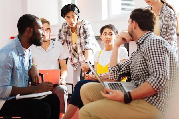 Student beantwoordt. verlegen jong meisje houdt haar aantekeningen vast en spreekt terwijl medestudenten naast haar zitten en aandachtig naar haar woorden luisteren