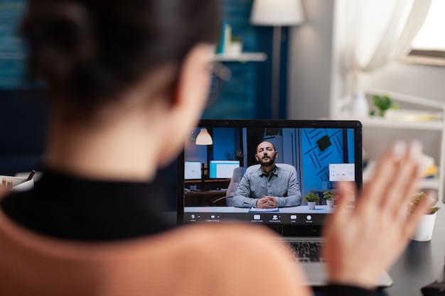 Student begroet haar universitair docent tijdens virtuele vergadering met behulp van laptopcomputer. blanke vrouw studeert literatuurschool webinar terwijl ze aan een bureautafel in de woonkamer zit