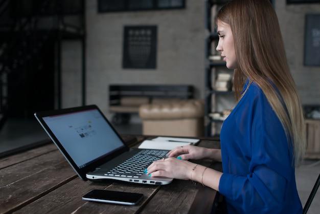 Student bereidt zich voor op lessen die op internet surfen op haar laptop aan tafel in trendy café.