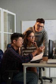 Student computerwetenschappen legt zijn creatieve idee uit aan vrienden wanneer ze aan een groepsproject werken