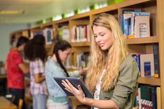Student die digitale tablet in bibliotheek gebruikt