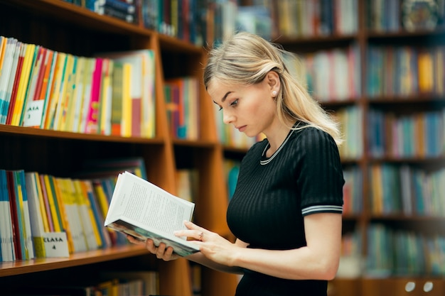 Student die een boek in de bibliotheek leest