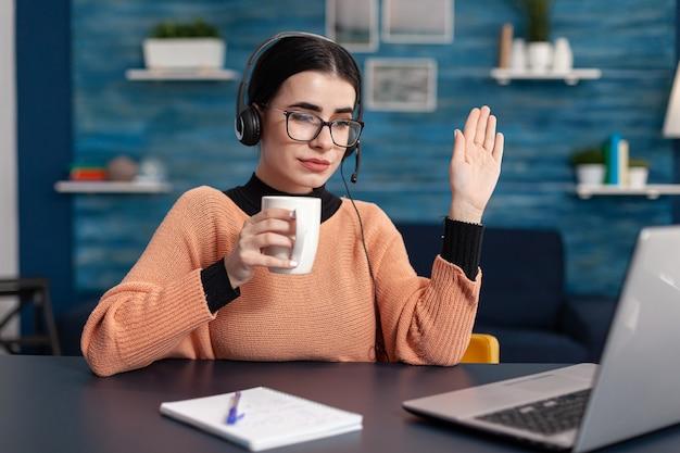 Student die een kopje koffie vasthoudt terwijl ze naar haar leraar luistert tijdens een videogesprekconferentie op een laptopcomputer. vrouw die communicatie-informatie bestudeert met behulp van e-learning college-platform
