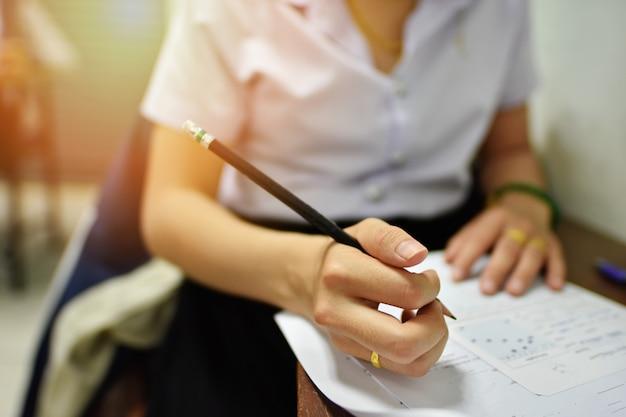 Student die een potlood houdt dat schriftelijke test neemt of dingtaakopdracht in het klaslokaal