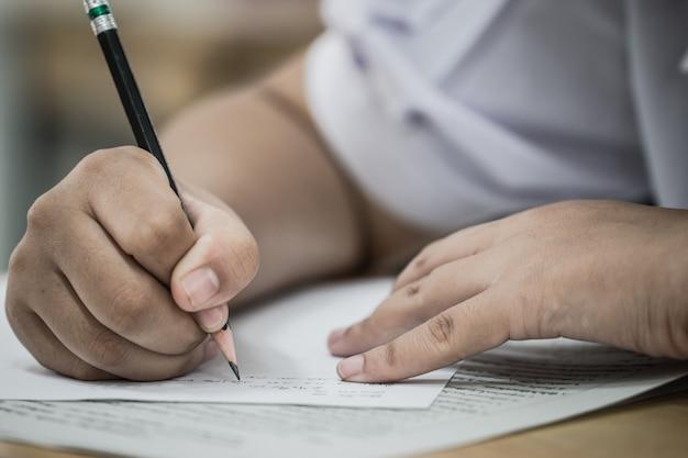 Student die examens neemt, schrijft onderzoek op papier antwoordblad optische vorm van gestandaardiseerde test