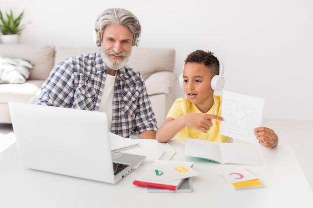 Student die geometrische vormen tonen bij laptop dichtbij leraar
