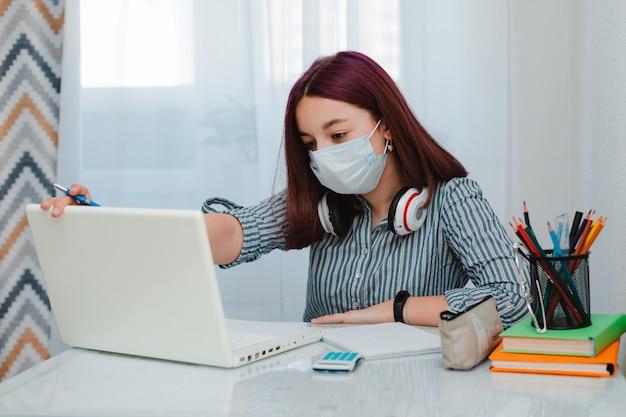 Student die huis bestuderen die met haar laptop werken die thuiswerk dicht omhoog doen. concept onderwijs op afstand tijdens quarantaine