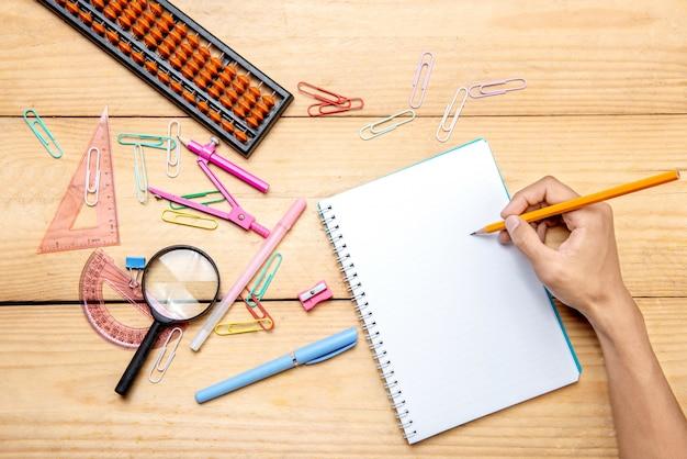 Student die in notitieboekje met schoollevering en kantoorbehoeften op de houten lijst schrijft