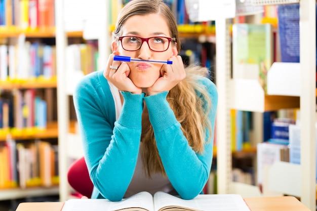 Student die met boeken in bibliotheek leert