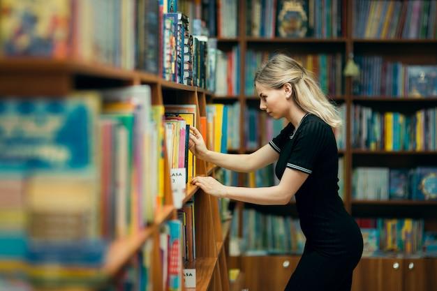 Student die naar boeken in een bibliotheek zoekt