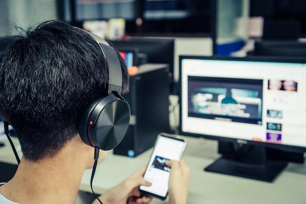 Student die online studieconcept leren: aziatische jonge mens die met hoofdtelefoons en laptop luistert