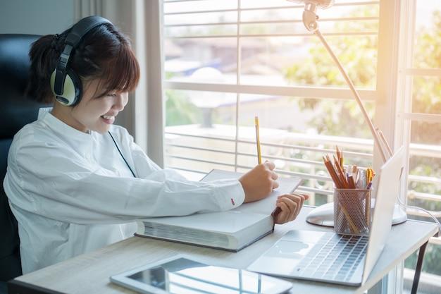 Student die online studieconcept leren: mooi aziatisch meisje dat met hoofdtelefoons en laptop luistert