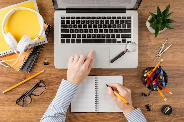 Student die op een notitieboekje op bureau schrijft