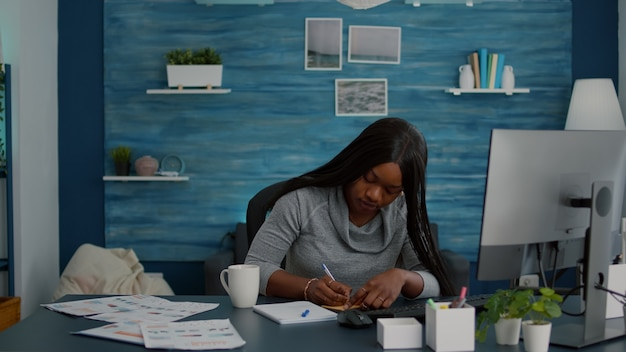 Student die schoolideeën schrijft op plaknotities die aan huiswerk werken aan een bureautafel in de woonkamer