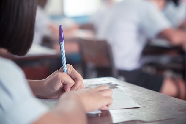 Student die test of examen in klaslokaal van school met spanning doet