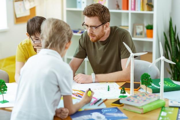 Student die vragen stelt. geconcentreerde bebaarde man met een heldere bril die bij zijn studenten zit en een poster trekt