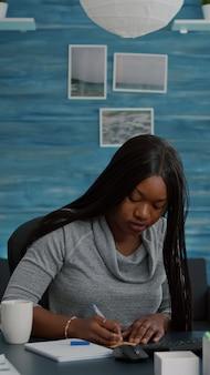 Student die zakelijke ideeën schrijft op plaknotities die op de computer werken en huiswerk op school doen