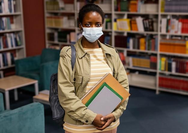 Student draagt een gezichtsmasker in de bibliotheek
