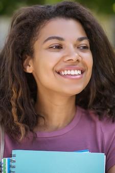 Student. een foto van een meisje in een roze t-shirt met studieboeken in haar handen