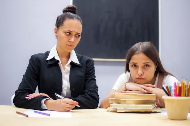 Student en student zitten aan een bureau in het schoolkantoor