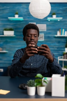Student-gamer die telefoon in horizontale positie houdt