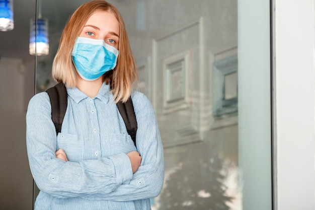 Student girl met gekruiste armen op universiteitsinterieur tijdens coronavirus covid lockdow. schoolmeisje in blauw masker met rugzak. jonge vrouwelijke student met beschermend medisch masker.