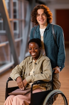 Student helpt een collega in een rolstoel