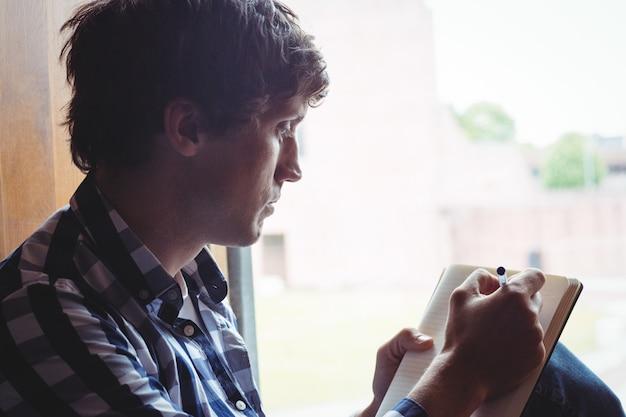 Student het schrijven van notities in de buurt van venster