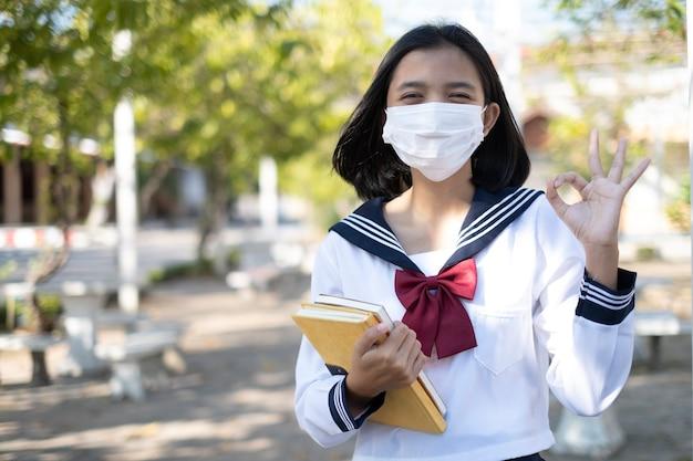 Student houdt boek vast en draagt masker in schooluniform