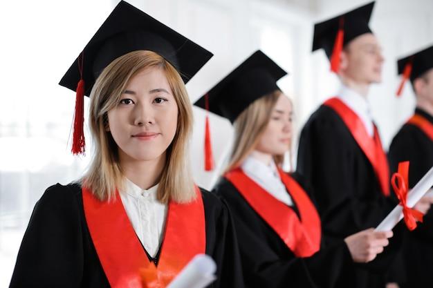 Student in bachelor gewaad met diploma binnenshuis. afstudeerdag