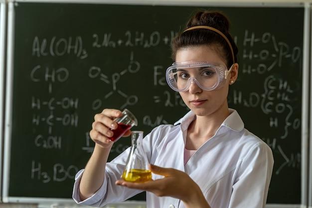 Student in witte jas experiment test doen in scheikunde laboratorium met vloeibare formule, onderwijs
