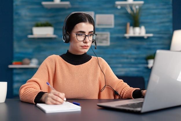Student informatie zoeken op internet voor universitair examen met behulp van laptopcomputer. geconcentreerde vrouw die haar huiswerk doet met behulp van e-learningplatform terwijl ze aan een bureau in de woonkamer zit