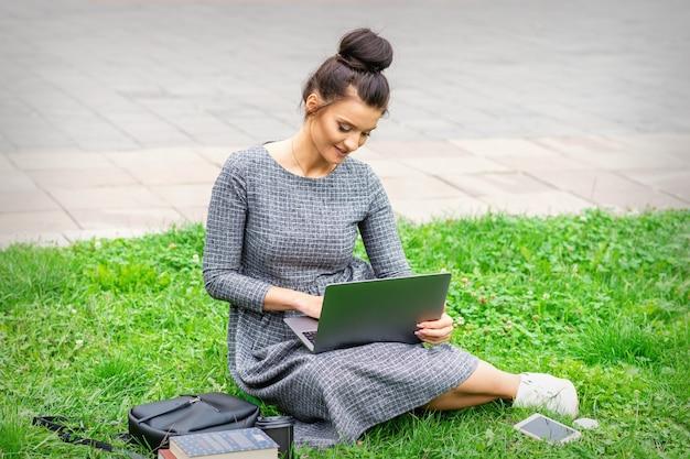 Student jonge blanke vrouw gebruikt laptop zittend op het gras op straat