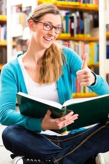 Student - jonge vrouw of meisjeszitting met boeken in bibliotheek het leren