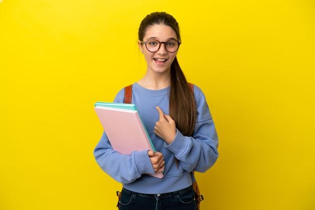 Student kind vrouw over geïsoleerde gele achtergrond met verrassing gezichtsuitdrukking