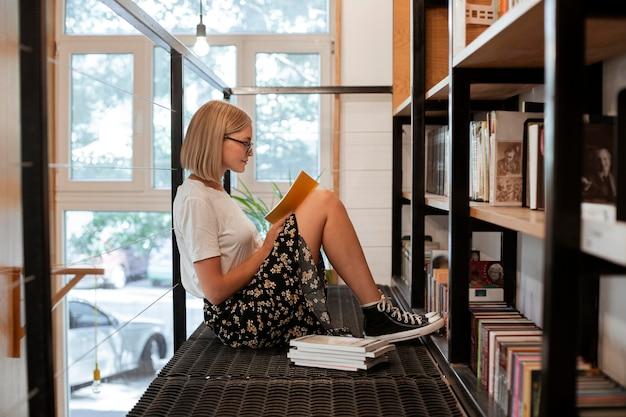Student leest een boek in de bibliotheek