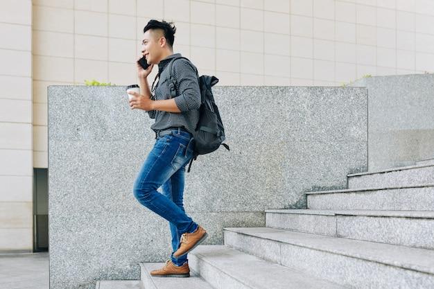 Student lopen en bellen op de telefoon