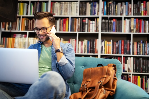 Student man in bibliotheek praten op mobiele telefoon en werken op laptop