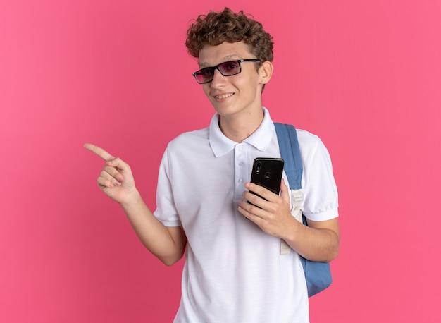 Student man in casual kleding met bril met rugzak met smartphone wijzend met wijsvinger naar de zijkant glimlachend vrolijk staande over roze achtergrond