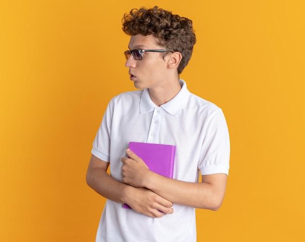 Student man in casual kleding met een bril die een boek vasthoudt en verward opzij kijkt