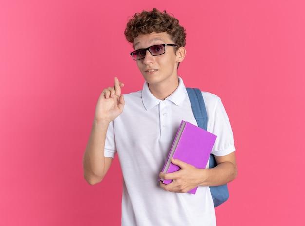 Student man in casual kleding met een bril met rugzak die een notitieboekje vasthoudt en naar de camera kijkt die lacht en belooft dat hij zijn vingers kruist