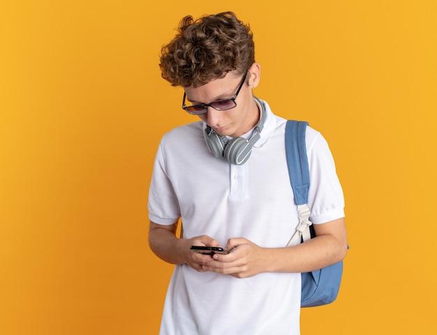 Student man in casual kleding met koptelefoon met bril met rugzak met smartphone schrijven bericht met serieus gezicht staande over oranje achtergrond